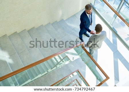 High angle view of smiling bearded businessman greeting his young colleague with handshake while standing on staircase landing of modern office building