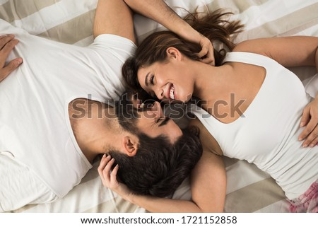 High angle view of smiling couple relaxing and lying down in bed .They are looking at each other
