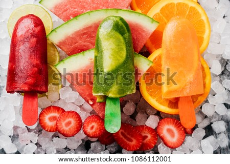 high angle view of some different homemade ice pops, made with different natural fruit juices and pieces of fruit, such as watermelon, strawberry, peach, lime or orange, placed on ice #1086112001