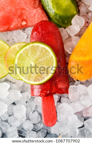 high angle view of some different homemade ice pops, made with different natural fruit juices and pieces of fruit, such as watermelon, lime or orange, placed on crushed ice #1087707902
