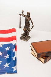 high angle view of statuette of justice near american flag and books isolated on white