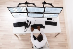 High Angle View Of Stock Market Broker Looking At Graphs On Computer