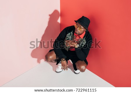 high angle view of stylish african american man crouching and looking away in studio #722961115