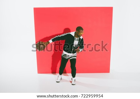 high angle view of stylish african american man playing basketball in studio #722959954