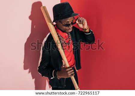 high angle view of stylish african american man with baseball bat adjusting sunglasses and looking away #722965117