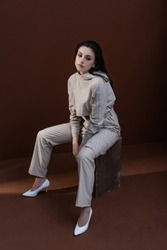 high angle view of stylish woman in trendy wear sitting on box with brown background, looking away