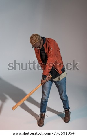 high angle view of stylish young african american man playing with baseball bat on grey #778531054