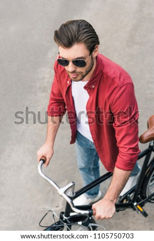 high angle view of stylish young man in sunglasses with bicycle  #1105750703