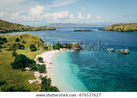 Shutterstock High angle view of sunny day Pink beach with turquoise water of Flores sea and tourist boat. The island is in Flores, Komodo islands, Indonesia.
