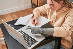 High angle view of the caucasian girl with artificial limb typing on keyboard while preparing her homework or working at home. Studying at the distance concept. Stock photo