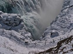 High angle view of the lower cascade of Gullfoss water fall in southwest Iceland, part of famous Golden Circle, in winter season with footpath, spraying water and bizarre looking ice formations.