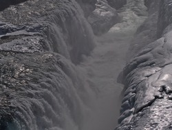 High angle view of the lower cascade of Gullfoss waterfall in southwestern Iceland, part of popular Golden Circle, in winter season with spraying water, deep gorge and bizarre looking ice formations.