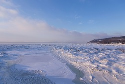 High angle view of the partly frozen St. Lawrence River seen during a hazy sunny winter morning with the Cap-Rouge Cape in the background, Quebec City, Quebec, Canada