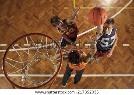 High angle view of three young men playing basketball