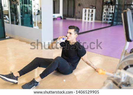 High angle view of tired young man drinking water while sitting on floor in health club