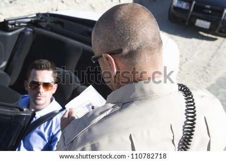 High angle view of traffic officer checking man's license