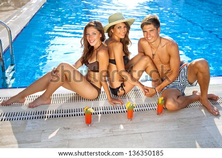 High angle view of two beautiful women in bikinis enjoying drinks at the edge of a sparkling blue swimming pool with a handsome young man
