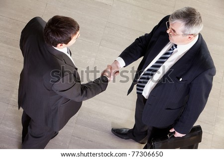 High angle view of two businessmen shaking hands
