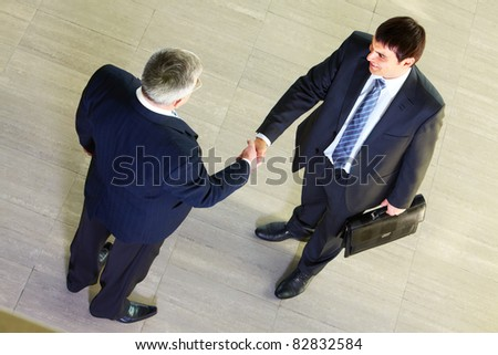 High angle view of two businessmen shaking hands after signing contract