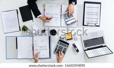 High Angle View Of Two Businesspeople Calculating Bills In Office ストックフォト ©