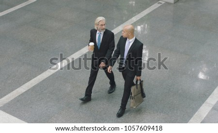 high angle view of two corporate executives talking while walking across lobby of modern office building.