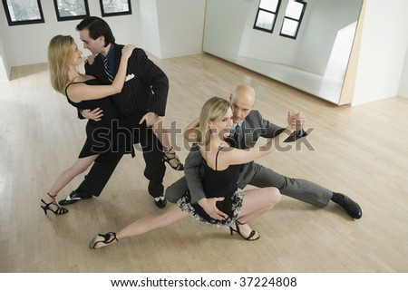 High angle view of two mid adult couples dancing Argentine Tango