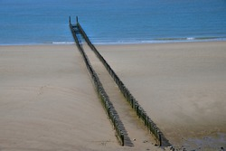 High angle view of two parallel rows of the typical wooden breakwaters on the sandy beach of the city of Westkapelle in the Netherlands ending in the sea