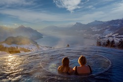 High angle view of two women in an infiniti pool high up the mountain overlooking the snowy mountains and large lake of Switzerland during sunset against a blue sky