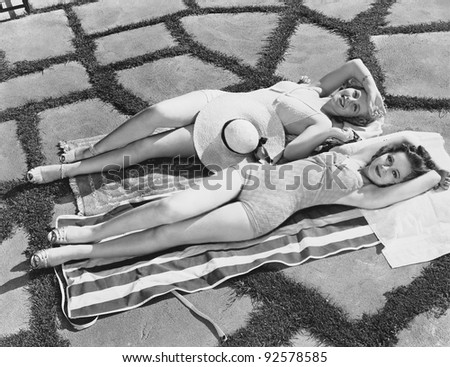 High angle view of two young women lying on a towel in the sun