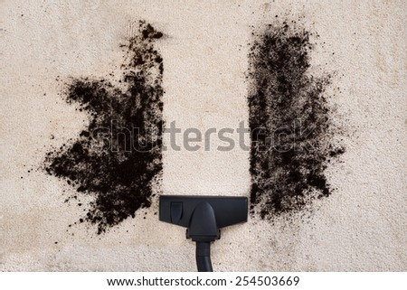 High Angle View Of Vacuum Cleaner Cleaning Dirt On Carpet