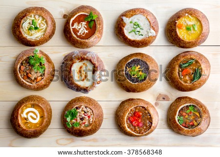 High Angle View of Various Comforting and Savory Gourmet Soups Served in Hollowed Out Bread Bowls on Wooden Table Surface