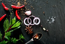 High Angle View of Various Fresh Herbs and Spices, Onion Slices, and Hot Peppers Scattered on Dark Gray Stone Surface with Copy Space