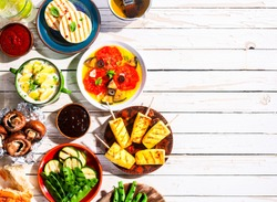High Angle View of Vegetarian Mediterranean Meal of Grilled Fruit and Vegetables Spread Out on White Wooden Picnic Table with Copy Space