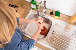 High Angle View Of Woman Using Plunger In Blocked Kitchen Sink To Unclog Drain