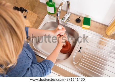 High Angle View Of Woman Using Plunger In Blocked Kitchen Sink To Unclog Drain - Shutterstock ID 571641430