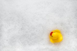 High Angle View of yellow rubber duck in bath swimming in foam water. Yellow rubber ducklings in soapy foam, fun for kids.