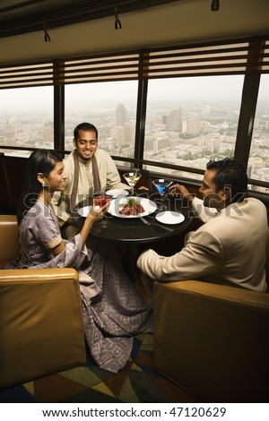 High angle view of young adult males and a female seated near a window in a high rise restaurant. Vertical shot.