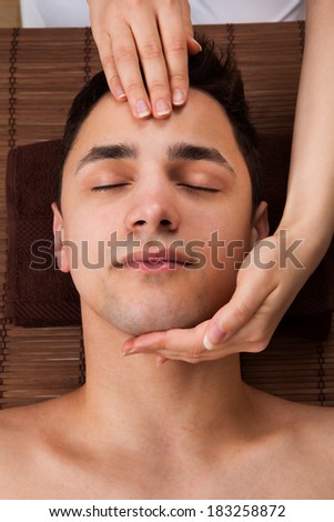 High angle view of young man receiving head massage from massager in spa