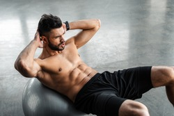 high angle view of young sportsman with bare chest doing abs exercise on fitness ball at gym