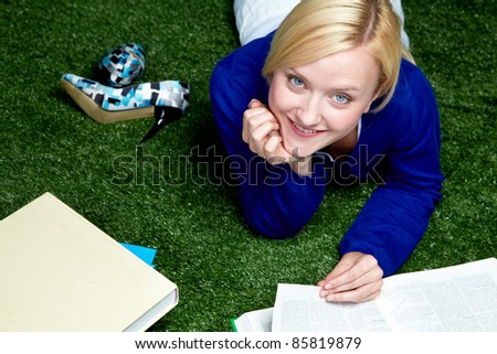 High angle view of young student lying on grass with textbooks