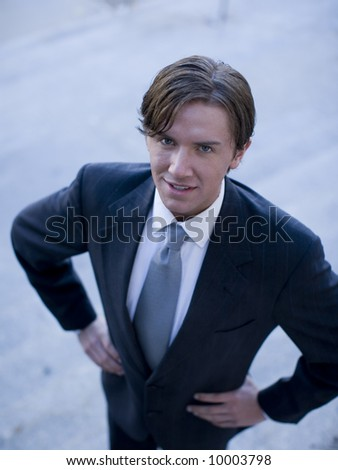 high-angle view of young white businessman standing wearing suit looking up at cameraman