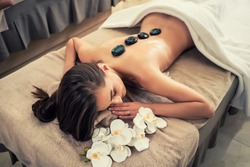 High angle view of young woman lying down on massage bed with traditional hot stones along the spine at spa and wellness center