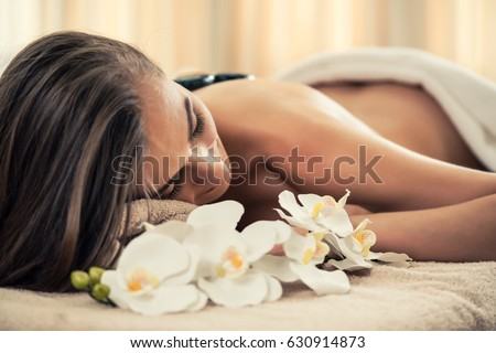 High angle view of young woman lying down on massage bed with traditional hot stones along the spine at spa and wellness center  #630914873