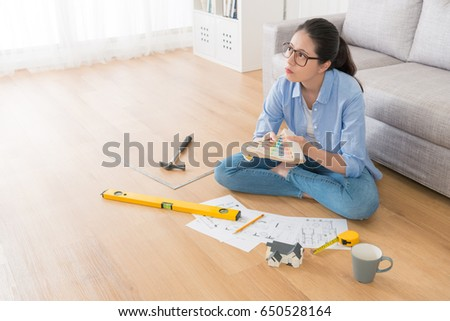 high angle view photo of designer holding color chart and thinking interior design sitting on living room wooden floor at home. #650528164