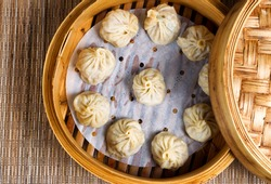 High angled view of cooked dumplings inside of bamboo steamer with lip partially off.