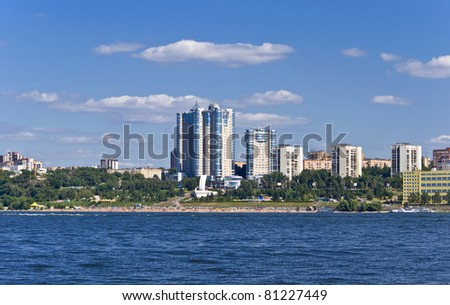 High apartment buildings on the quay. Beach filled with people. Summer urban landscape with a river. Samara. Russia. - stock photo