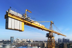 High building construction site. Big industrial tower crane with blue sky amd cityscape on background. Concrete plates weight balance. Counterweight. Aerial drone view. Metropolis city development.