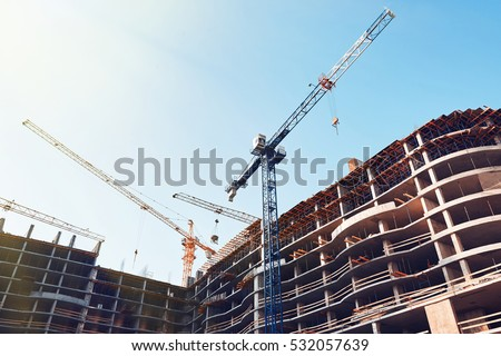 High building under construction. Side with cranes against blue sky with sun glare.