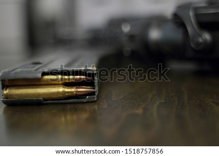 High capacity magazine with bullets next to an AR15 on a table in a home.