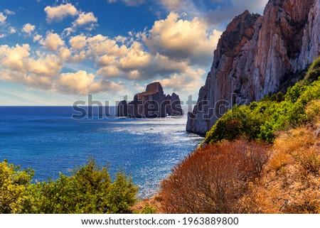"High cliffs of Mediterranean coast, ""Pan di Zucchero"" stack rock in Masua, west coast of Sardinia, Italy. Concali Su Terrainu with Porto Corallo on background. Sardinia island, Italy, Europe."